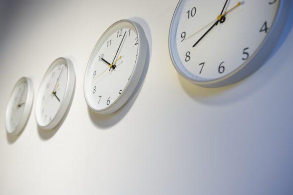 Vier Wanduhren mit unterschiedlichen Uhrzeiten