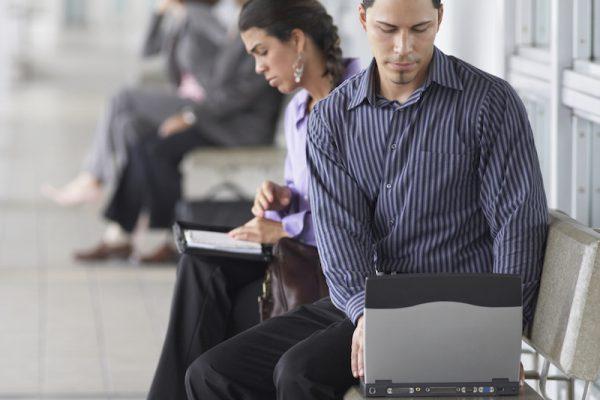 Junger Mann, der auf einer Bank sitzend am Laptop arbeitet