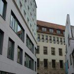 Neubau vor historischem Hintergrund