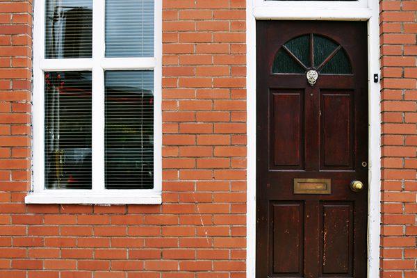 Hausfassade aus Ziegelsteinen mit Tür und Fenster