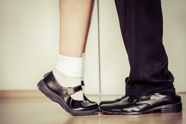 Frau auf Zehenspitzen vor Mann