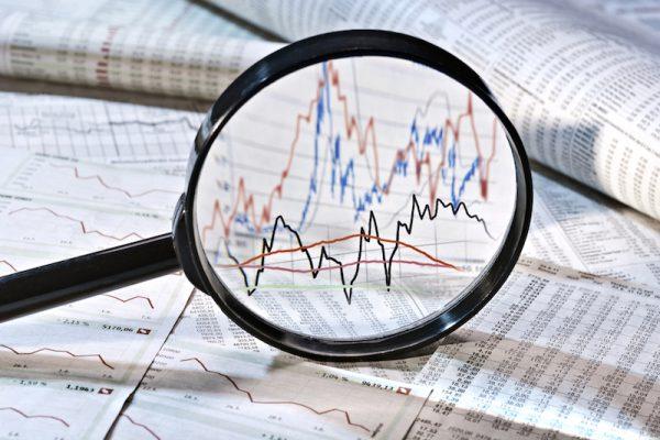 Blick mit Lupe auf Aktienkurs
