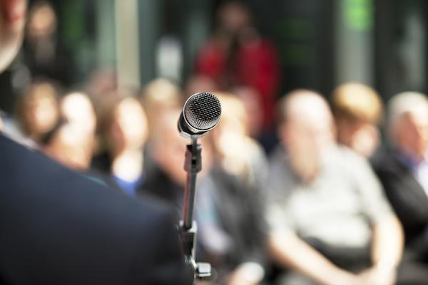 Vor Mikrofon stehender Mann; im Hintergrund sitzendes Publikum