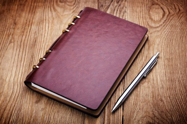 Weinrotes Notizbuch und silberner Kugelschreiber