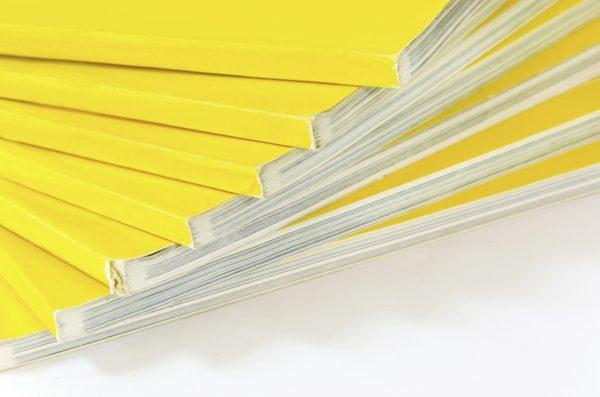 Fächerartig angeordneter Stapel aus Magazinen mit gelbem Umschlag
